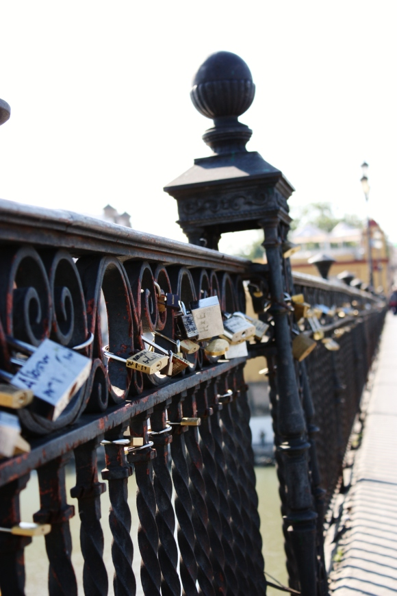 Padlocks on the Puente Isabelle II (Trianan Bridge) by Alex Mendez in Seville, Spain. A tradition where lovers fasten locks and then throw the key into the Guadalquivir river.